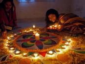 Kolkata: A girl makes a Rangoli ahead of Diwali in Kolkata, on Oct.21, 2014. (Photo: Kuntal Chakrabarty/IANS)